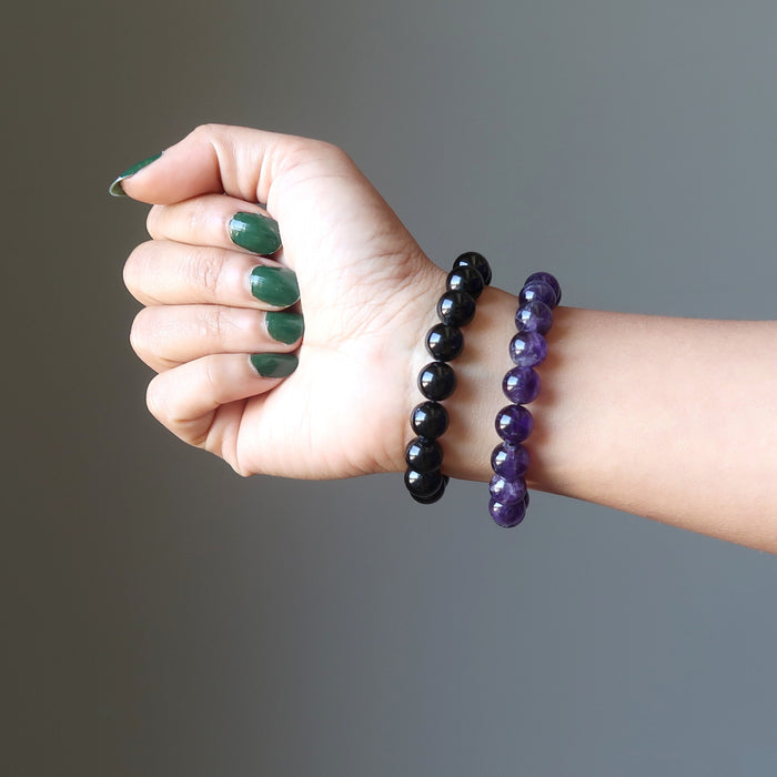 female hand wearing black tourmaline and amethyst bracelet set