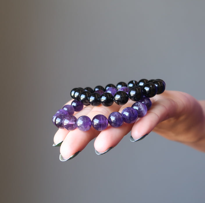 female hand with black tourmaline and amethyst bracelet set in palm