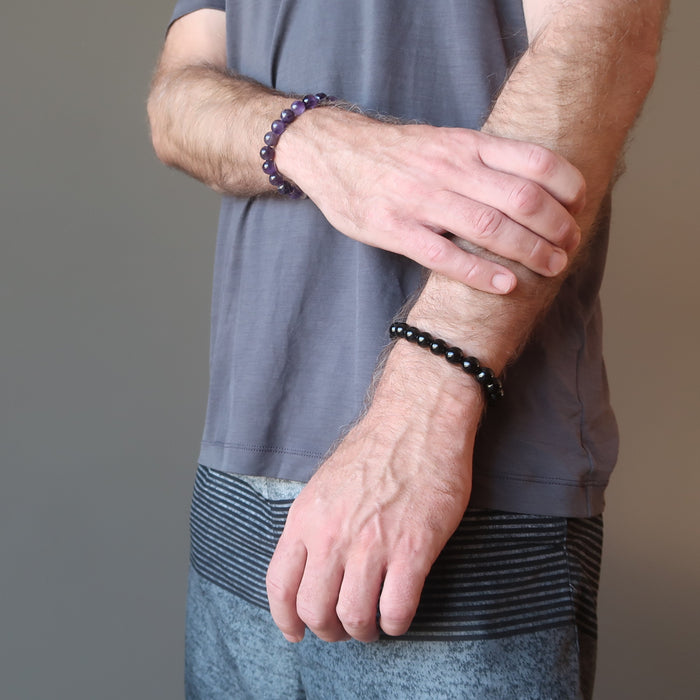 man wearing amethyst bracelet on one wrist and black tourmaline bracelet on the other