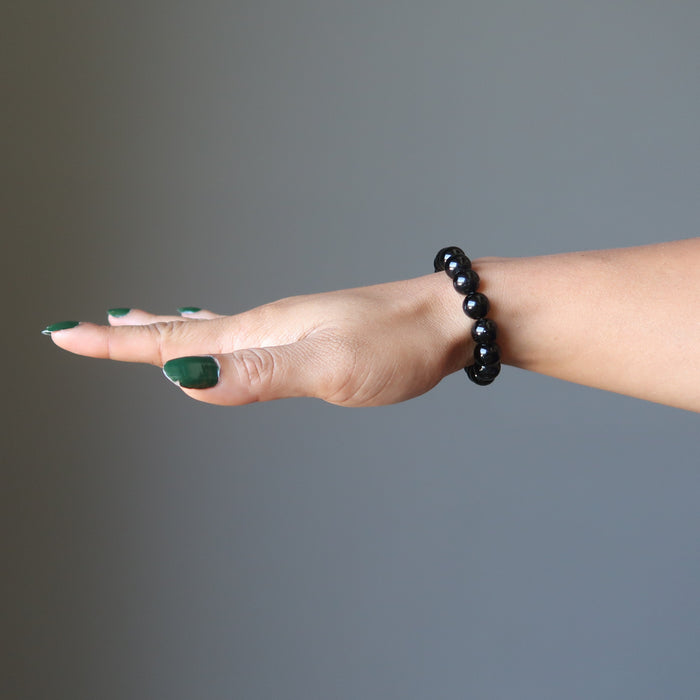 female hand wearing black tourmaline bracelet
