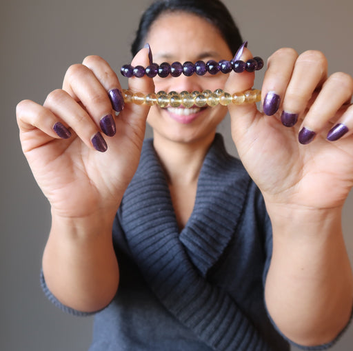 sheila of satin crystals holding up citrine and amethyst bracelets