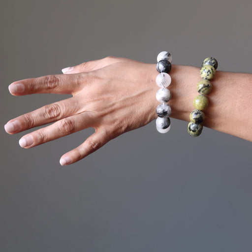 female hand modeling tourmaline quartz and serpentine bracelet set