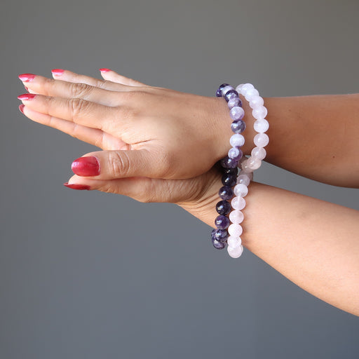 female hands clasped together both modeling amethyst and rose quartz bracelet sets