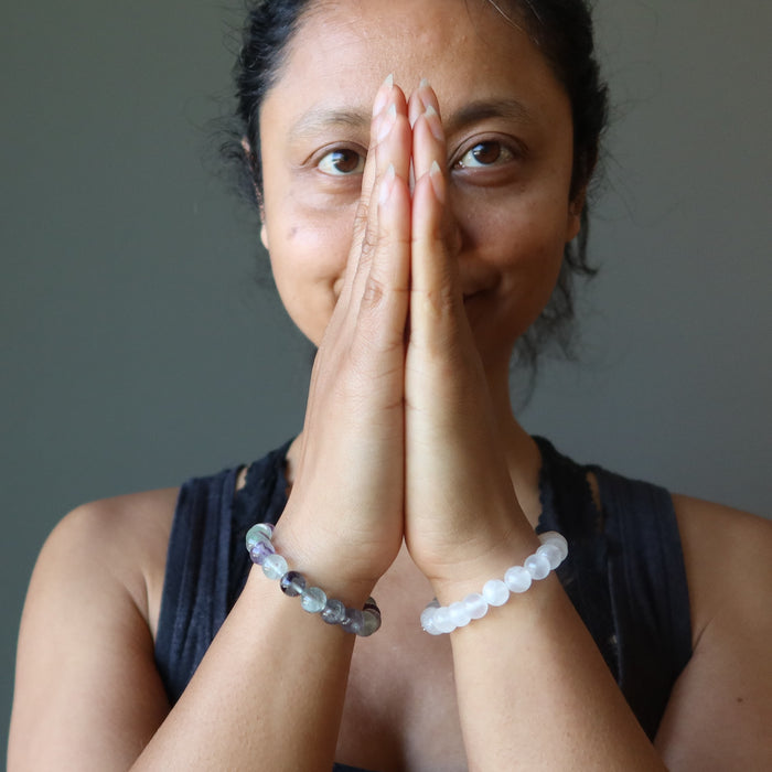 Sheila Satin of Satin Crystals has her hands in prayer to display rainbow fluorite bracelet on one arm and white selenite bracelet on the other