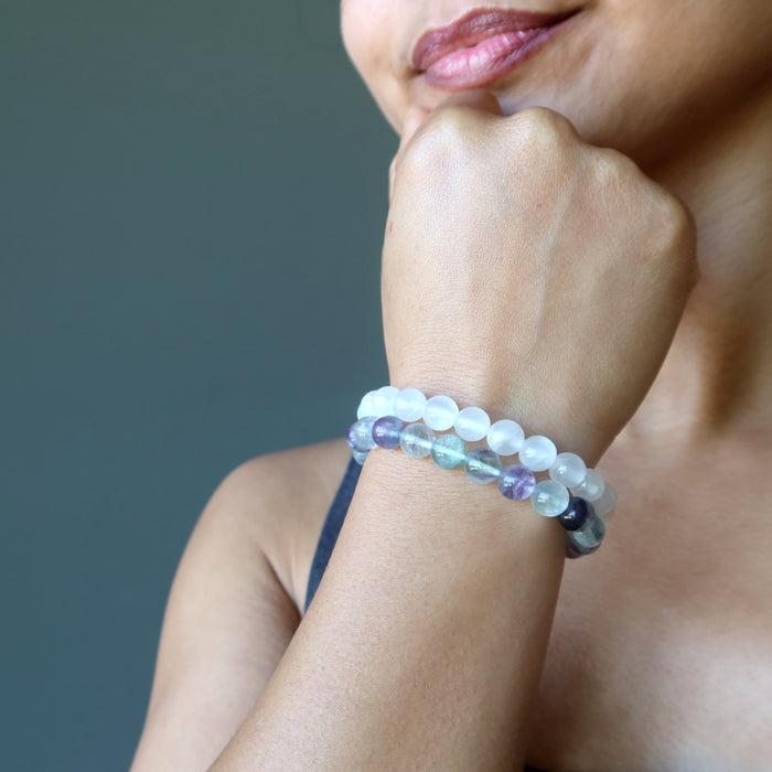 Sheila of Satin Crystals has her head to her chin white wearing the selenite fluorite stretch bracelet set