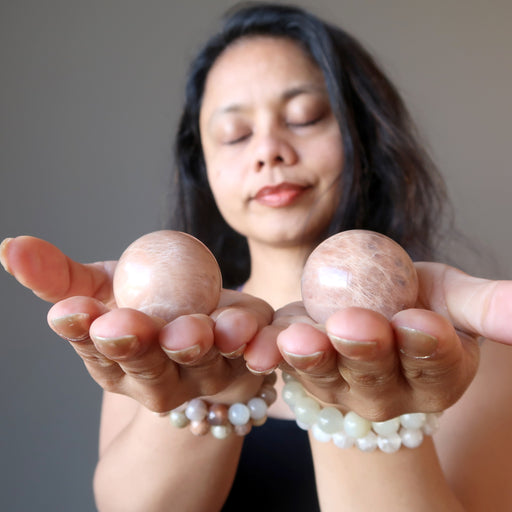 sheila of satin crystals meditating with two peach moonstone spheres