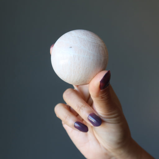 hand holding cream moonstone sphere