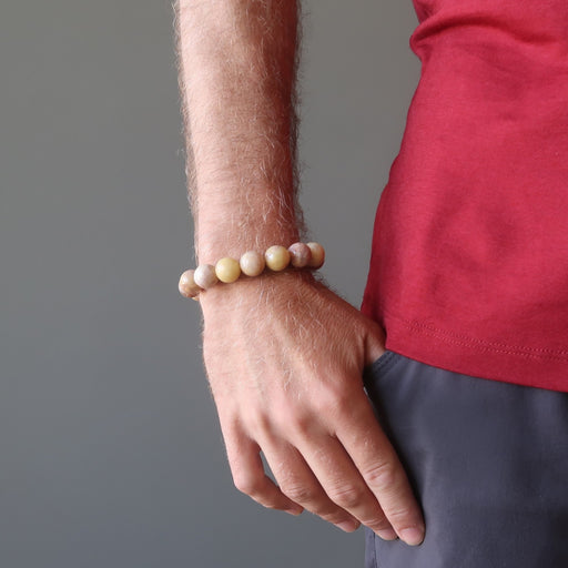 man's hand in pants pocket wearing yellow peach moonstone round stretch bracelet