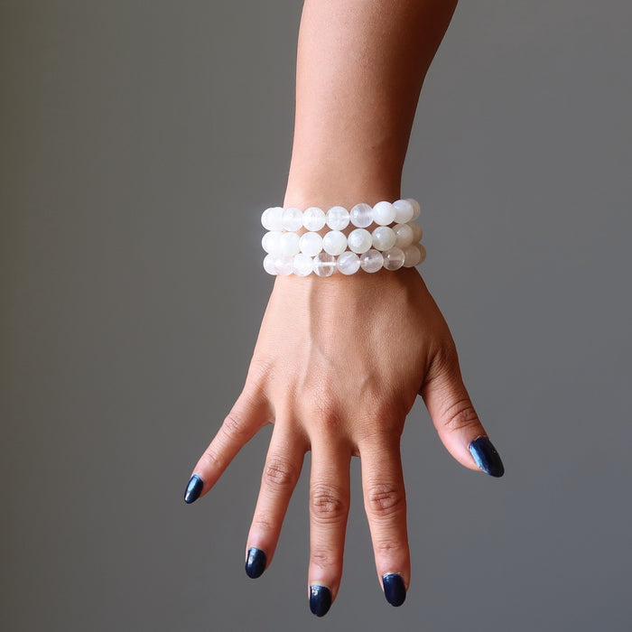 hand wearing white rainbow moonstone beaded stretch bracelets
