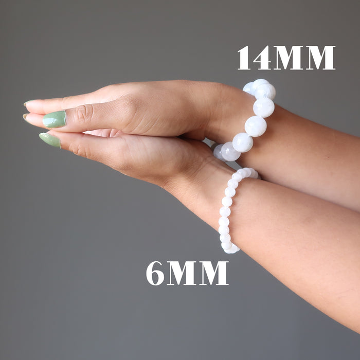hands clasped wearing 6mm and 14mm rainbow moonstone bracelet on each wrist