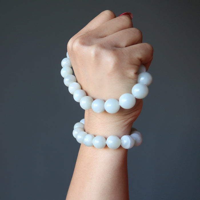hand holding and wearing white moonstone bracelets