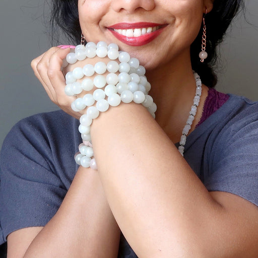 model with a stack of white moonstone bracelets