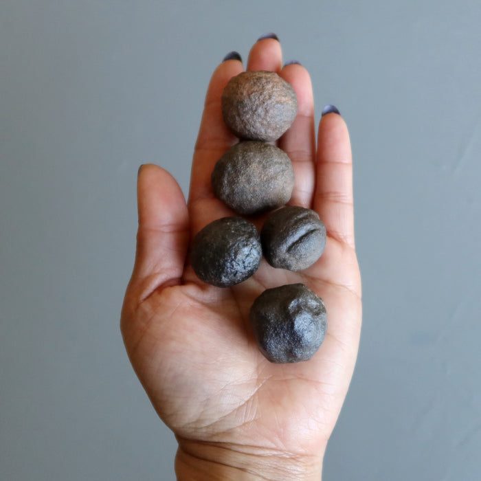 set of 5 brown moqui marble stones in palm of hand