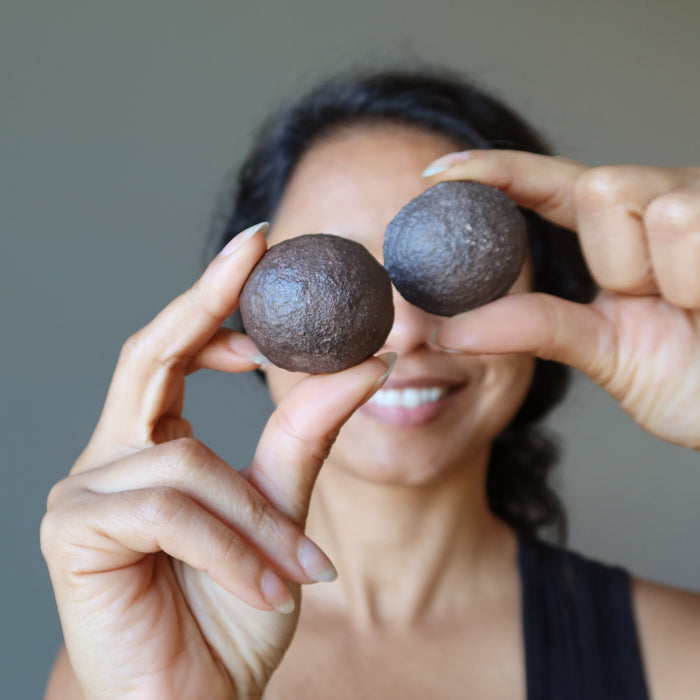 sheila of satin crystals holding pair of moqui marble stones in front of her eyes