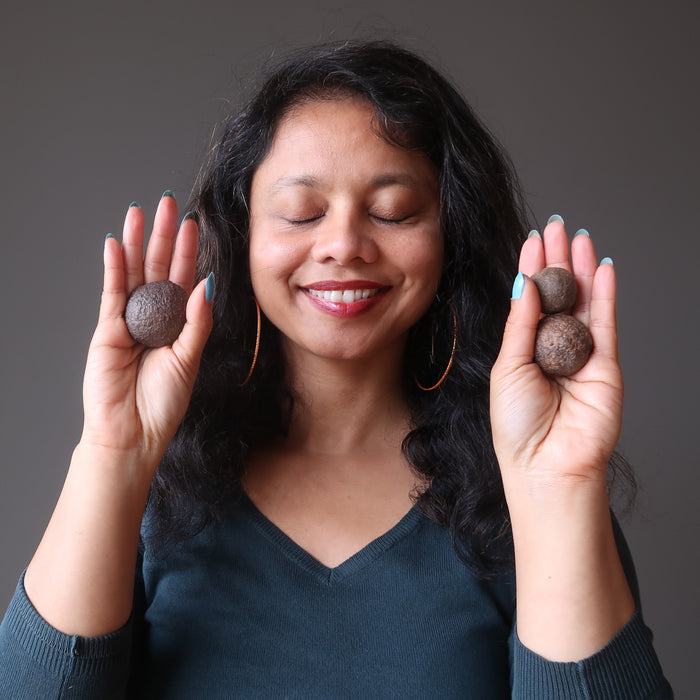 sheila of satincrystals holding set of three moqui marble stones in ascending sizes in her palms