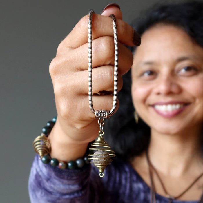 sheila of satin crystals holding moqui marble stone in vintage cage on antique copper snake chain necklace