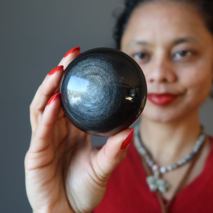 sheila of satin crystals gazing at a silver sheen obsidian sphere
