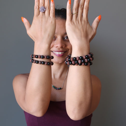 sheila of satin crystals with both hands raised wearing stacks of black obsidian and red lava bracelets