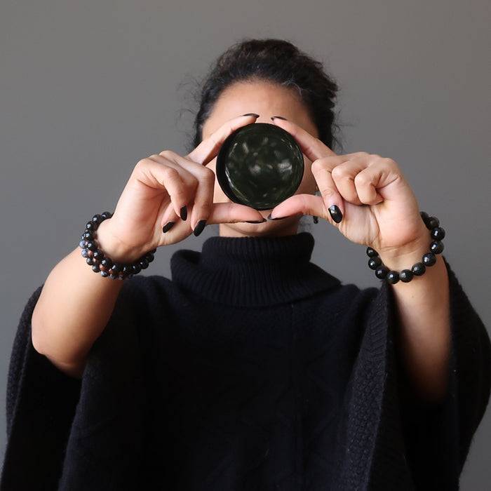 sheila of satin crystals holding an obsidian mirror in front of her face