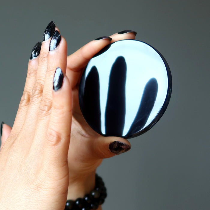 black obsidian circle mirror stone reflecting fingers held in front of it