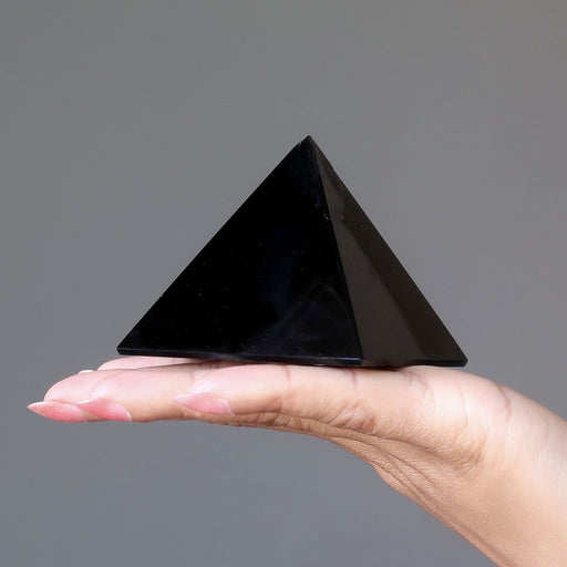 black obsidian pyramid on palm of hand
