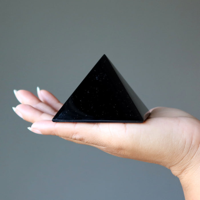 black obsidian pyramid in palm of hand