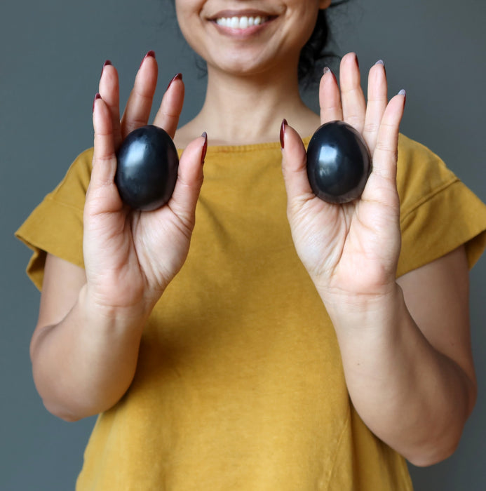 hands holding black obsidian eggs in each palm