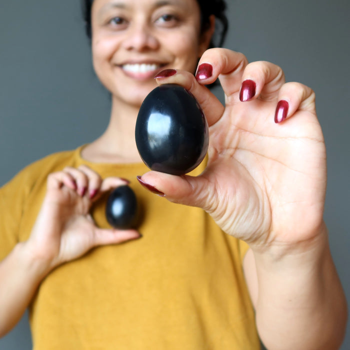 sheila of satin crystals holding two black obsidian eggs