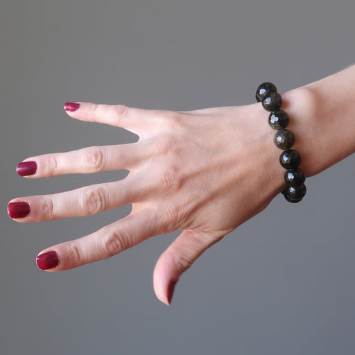 female hand modeling faceted gold sheen obsidian bracelet