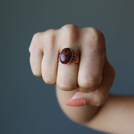 fist wearing mahogany obsidian oval in copper adjustable ring