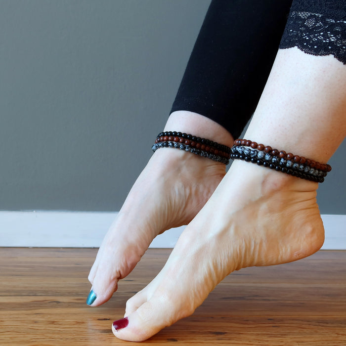 mahogany, snowflake and black obsidian anklets stacked on two different feet pointing toes