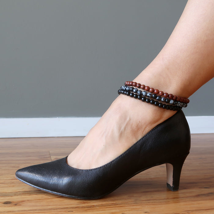 mahogany, snowflake and black obsidian anklets stacked on ankle in black heels