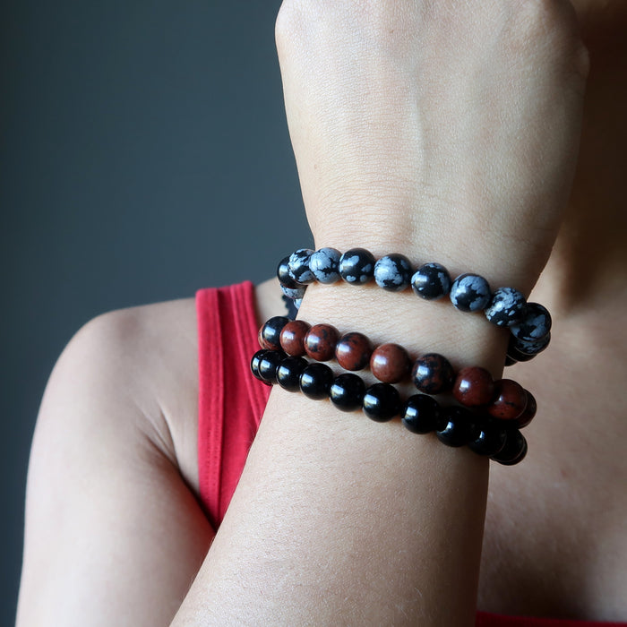 a lady models the obsidian bracelet three piece set on her wrist