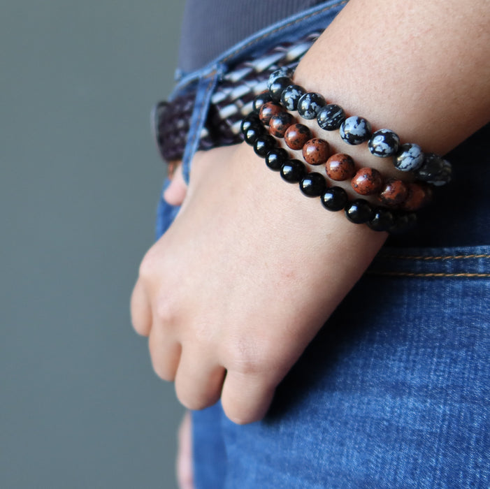 a lady models the black mahogany and snowflake obsidian triple set against her jeans