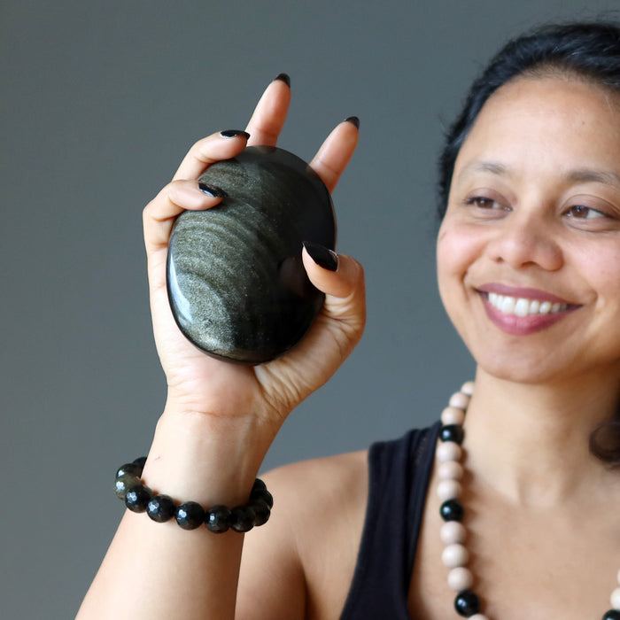 sheila of satin crystals holding up a big gold sheen obsidian palm stone