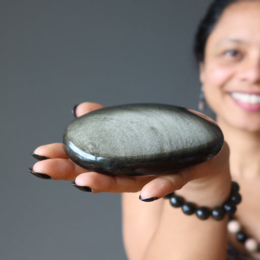 sheila of satin crystals holding gold sheen obsidian oval palm stone