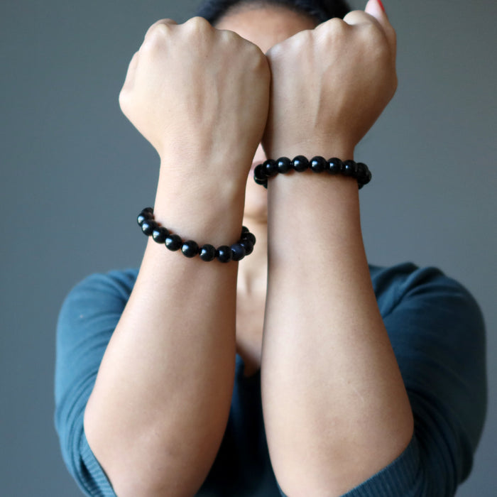 sheila of satin crystals with hands up wearing rainbow obsidian beaded stretch bracelets