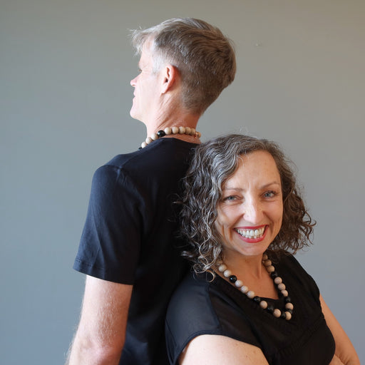 man and woman back to back wearing rainbow obsidian necklaces