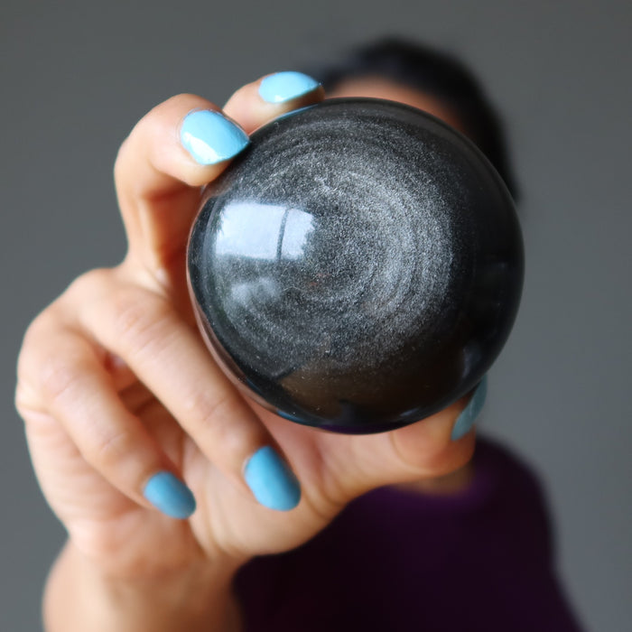 female holding silver sheen obsidian sphere in front of her face