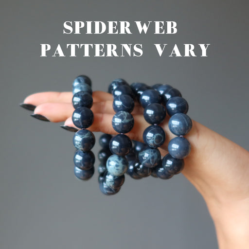 hand holding 4  round spiderweb obsidian stretch bracelets to show varying patterns
