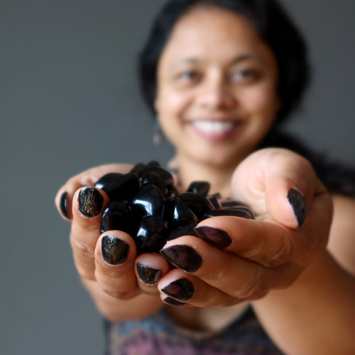 sheila of satin crystals holding 43 black obsidian tumbled stones