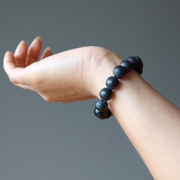 hand wearing a matte and polished glossy beaded round black onyx stretch bracelet