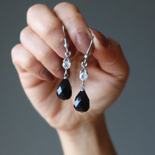 hands holding black onyx earrings