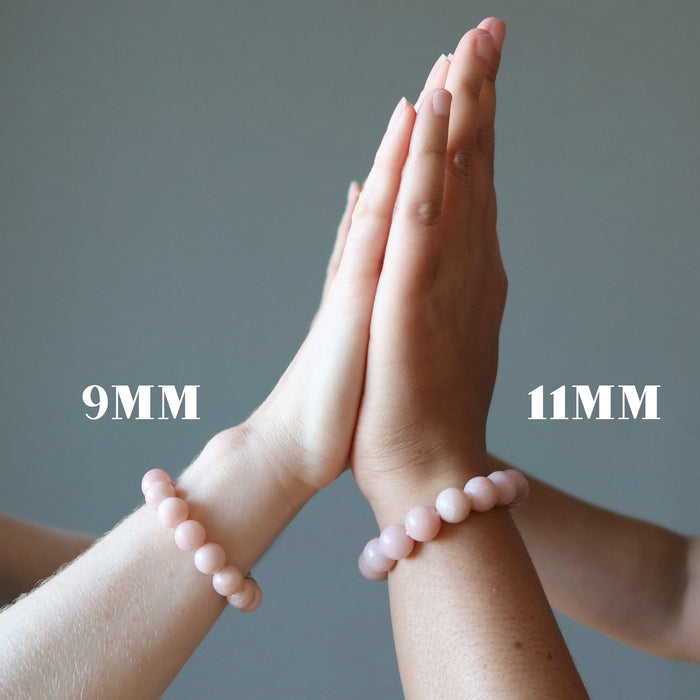 two people wearing pink opal bracelets on their wrists, one labeled at 9 and the other at 11 millimeters