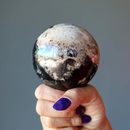 hand holding brown opal sphere