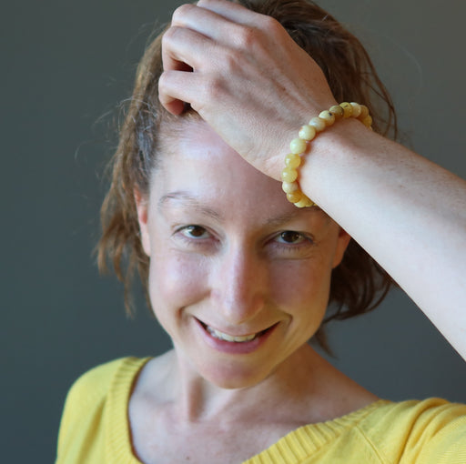 jamie of satin crystals with hand on her head wearing a round yellow opal beaded stretch bracelet