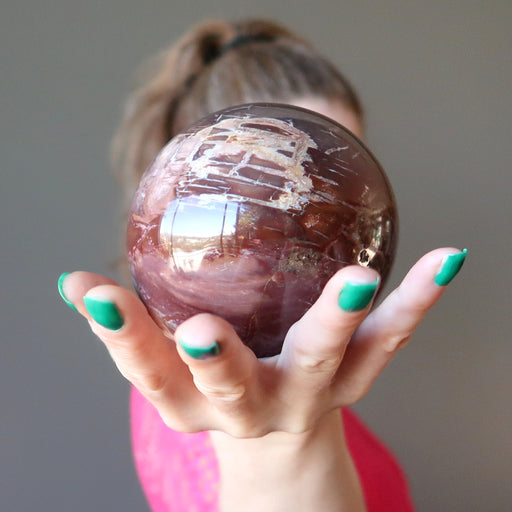 female holding petrified wood sphere in front of her face