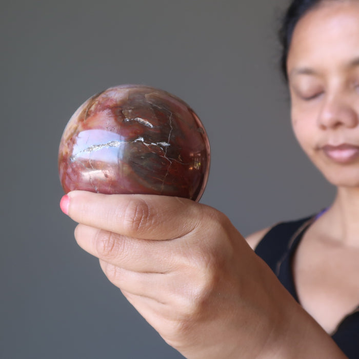 sheila of satin crystals meditating with a petrified wood ball