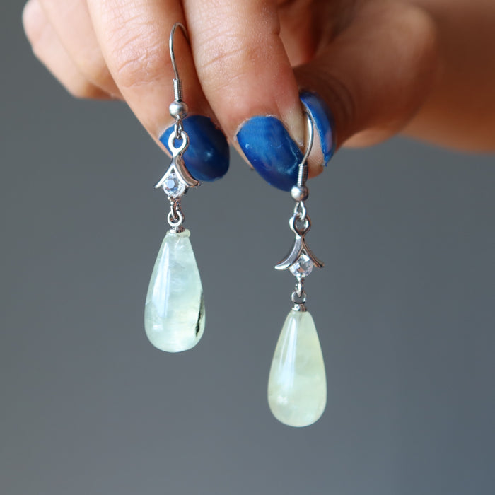 hand holding prehnite teardrop dangle earrings