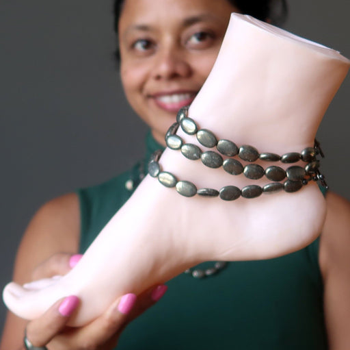sheila of satin crystals holding a mannequin foot wearing three pyrite anklets